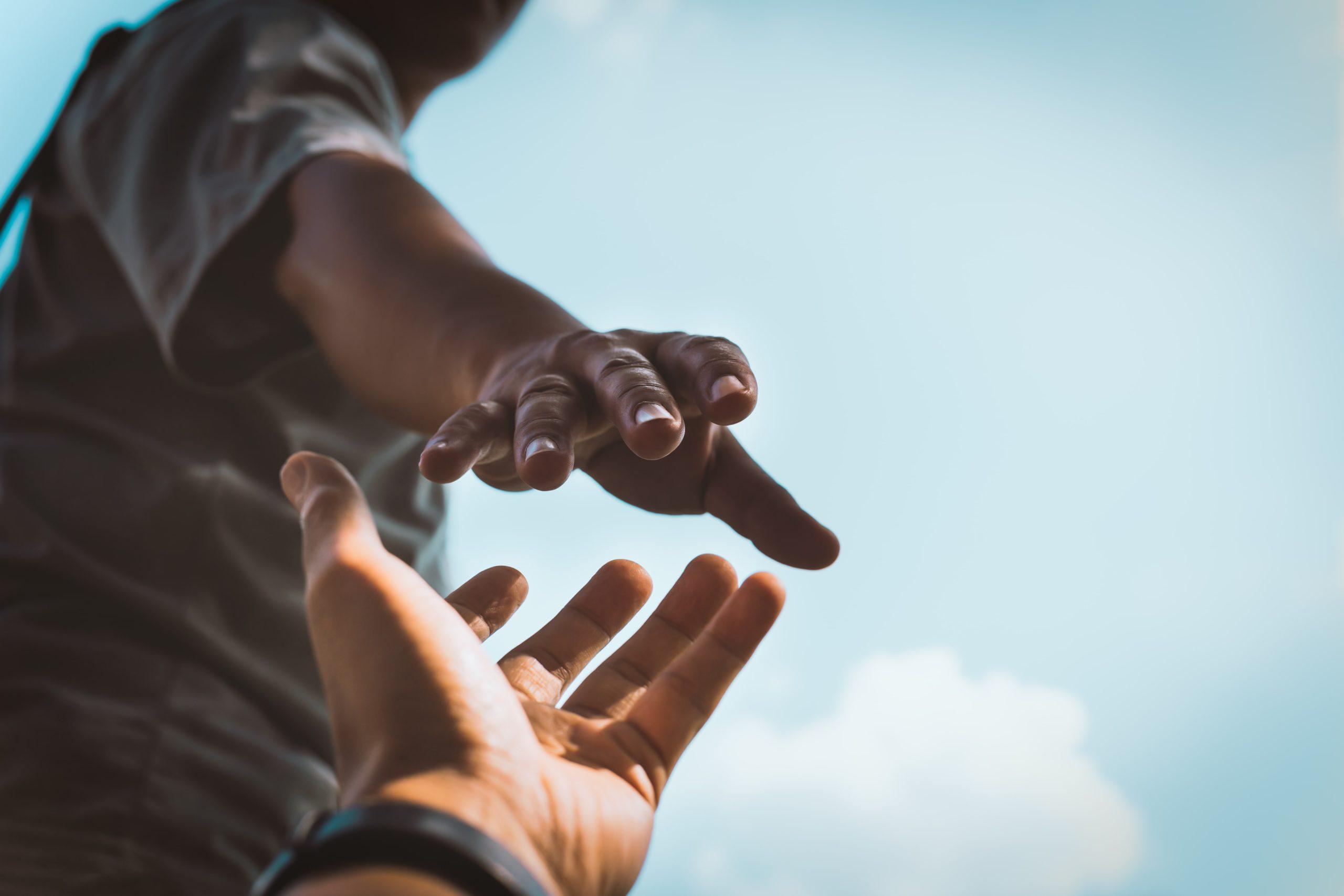 Twee handen reiken naar elkaar om goede doelen weer te geven